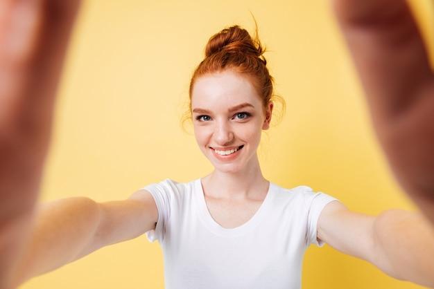 Улыбающаяся рыжая женщина в футболке делает селфи
