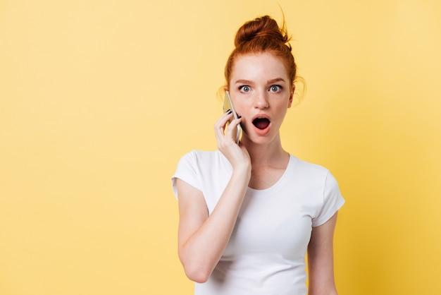 Потрясенная рыжая женщина в белой футболке разговаривает по смартфону
