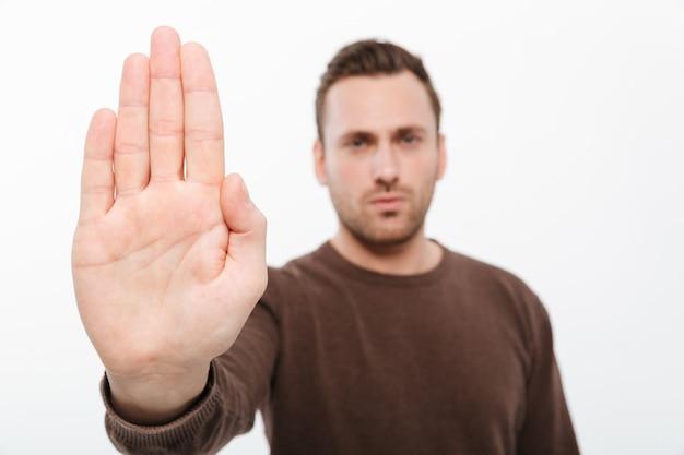 Красивый молодой серьезный человек, показаны стоп жест.