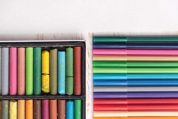 Вид сверху пастельной краски и маркеров в коробках на столе