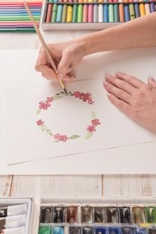 若いアーティストが水彩絵の具や職場でブラシで花のパターンを描画