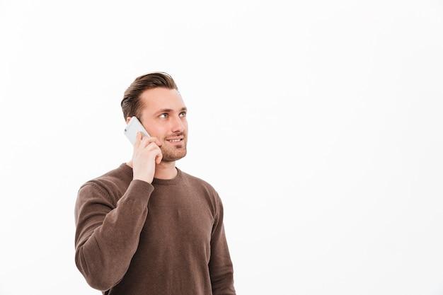 携帯電話で話している若い男の笑みを浮かべてください。よそ見。