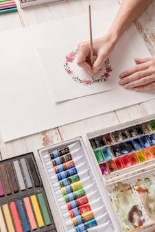 Молодой художник рисует цветочный узор акварельной краской и кистью на рабочем месте