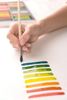 Художник рисует красочные полосы кистью на белой бумаге