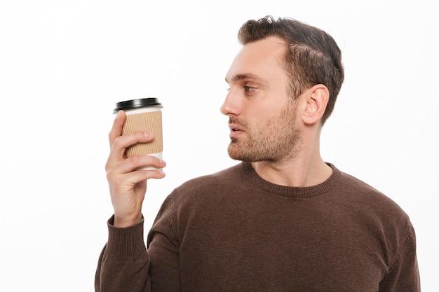 若い男がコーヒーを飲みます。よそ見。