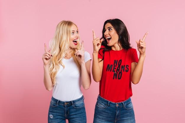 Две счастливые кричали женщины, показывая размер чего-то и глядя друг другу на розовом фоне