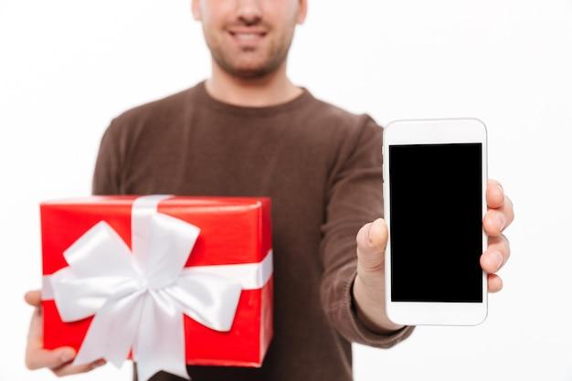 Улыбающийся молодой человек с подарочной коробкой