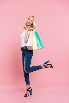 パッケージでポーズとピンクの上にカメラを見て幸せな金髪女の垂直側面図画像