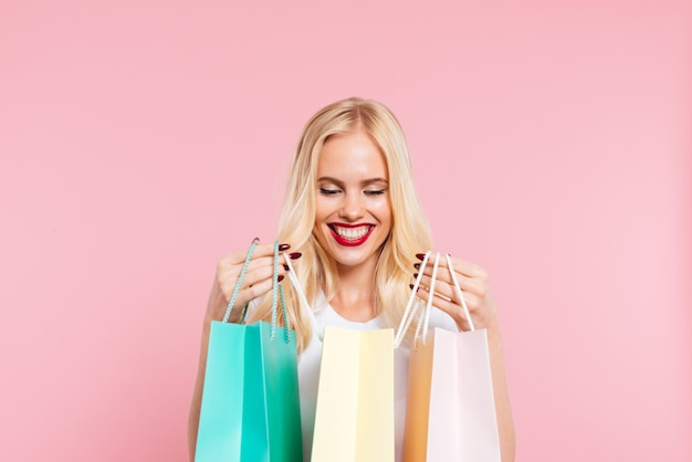ピンクの上にパッケージを見て満足している金髪の女性の画像