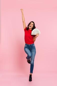 Полнометражное изображение счастливой брюнетки радуется и держит деньги, глядя на камеру над розовым