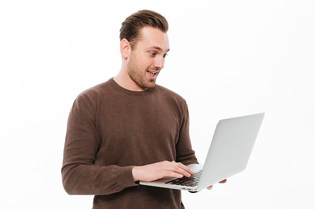 Возбужденный молодой человек, используя портативный компьютер.