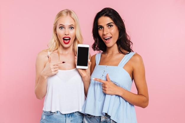 Удивленные улыбающиеся дамы, показывая пустой экран смартфона изолированы