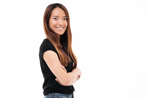 カメラを見て、組んだ手で立っている陽気な若いアジア女性のクローズアップの肖像画