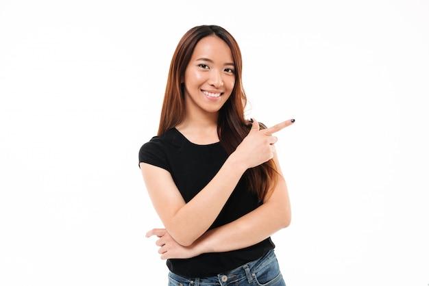 指で指している幸せな若いアジアの女の子のクローズアップの肖像画
