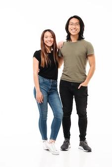 カメラ目線のカジュアルな服装で若い魅力的なアジアカップルの完全な長さの写真
