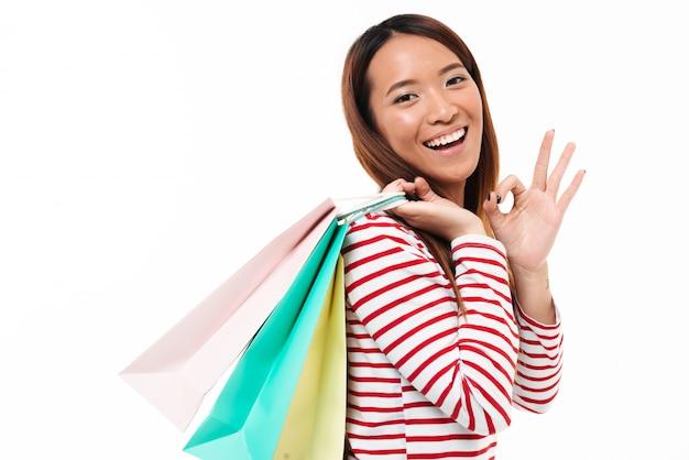 Портрет жизнерадостной азиатской девушки держа хозяйственные сумки