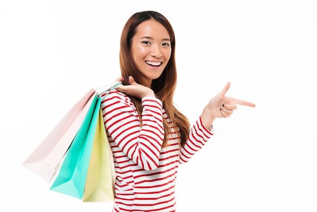 買い物袋を保持している幸せなアジアの少女の肖像画