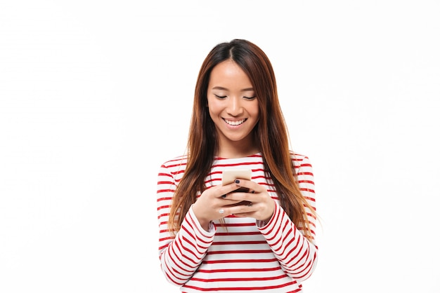 携帯電話を使用して笑顔の若いアジアの女の子の肖像画