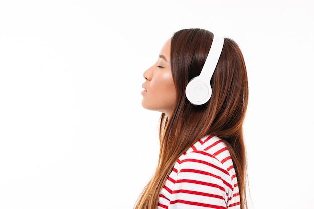 ヘッドフォンで若いアジアの女の子の側面図