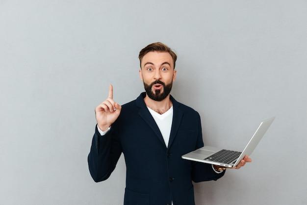 ラップトップコンピューターを保持し、灰色の上のカメラを見ながら考えを持つビジネス服で驚いてひげを生やした男