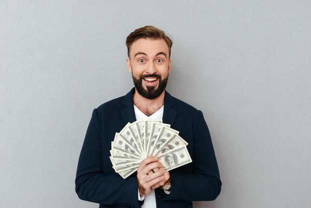 お金を押しながら灰色のカメラを見てビジネス服で驚いて幸せなひげを生やした男