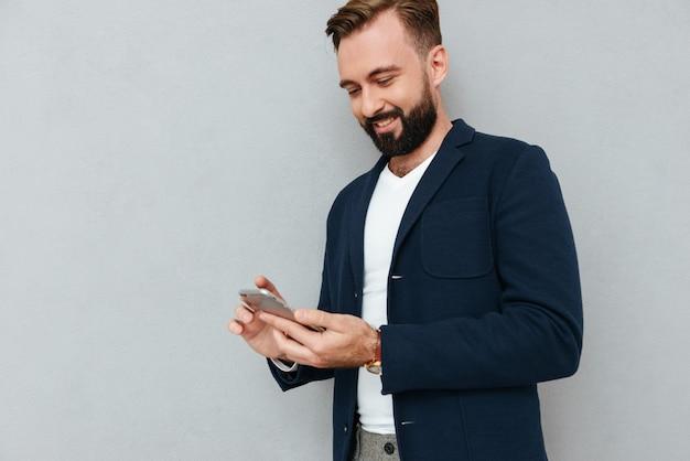 灰色で分離されたスマートフォンを使用して集中して男の笑みを浮かべてください。