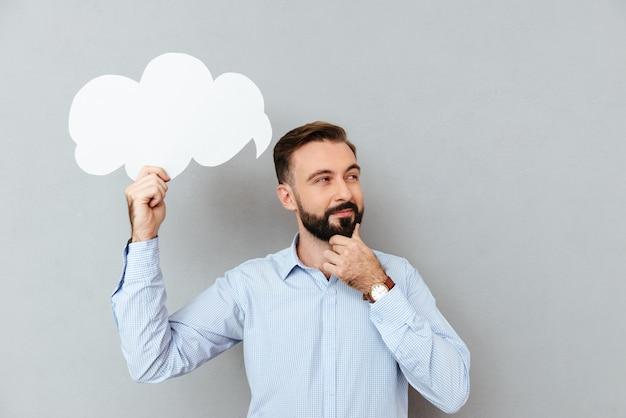 Задумчивый бородатый человек в деловой одежде держит пустое облако речи