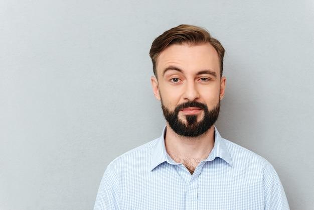 Насмешливый бородатый мужчина в деловой одежде смотрит в камеру