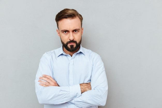 組んだ腕を持つビジネス服で深刻なひげを生やした男