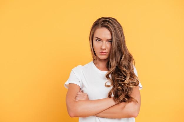 Сердитая молодая женщина, стоя со скрещенными руками