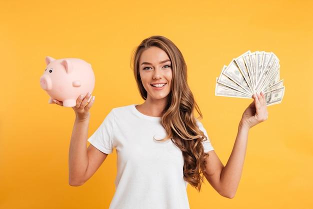 貯金箱を保持している陽気な若い女の子の肖像画