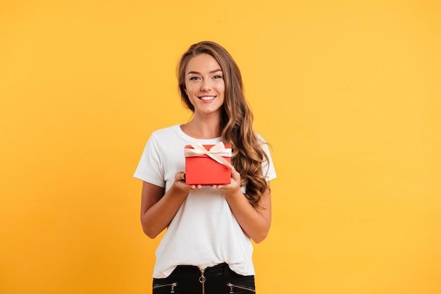 Портрет милой улыбающейся девушки с подарочной коробкой
