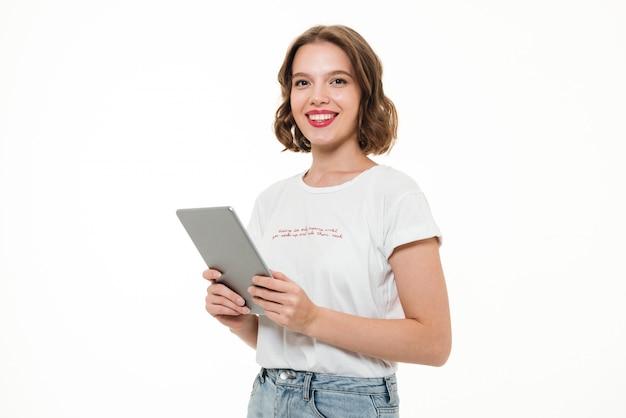 Портрет счастливой улыбающейся девушки, держащей планшетный компьютер