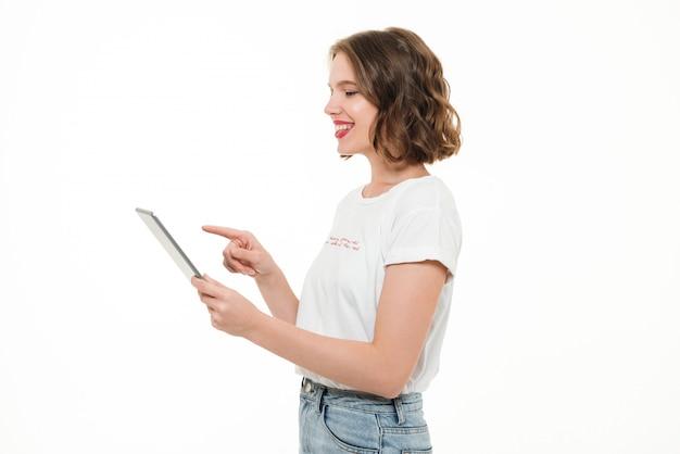 Портрет улыбающейся молодой девушки с помощью планшетного компьютера