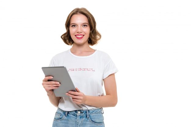 タブレットコンピューターを保持している陽気なかわいい女の子の肖像画