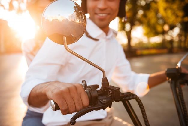 公園でモダンなバイクに乗って幸せなアフリカのカップルのトリミングされた画像