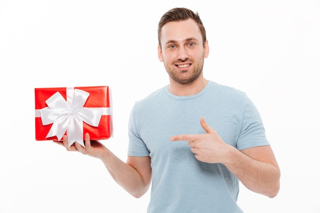 Изображение красивый парень с щетиной, улыбаясь и указывая указательным пальцем на красной подарочной коробке
