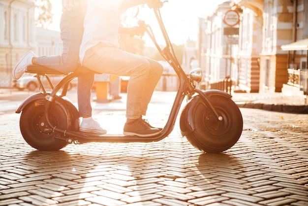 路上でモダンなバイクに乗る若いアフリカカップルの側面図をトリミング