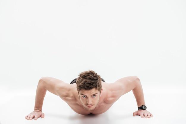 Сконцентрированный молодой спортсмен делает отжимания