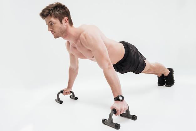 Молодой спортсмен подходит делать отжимания с решеткой