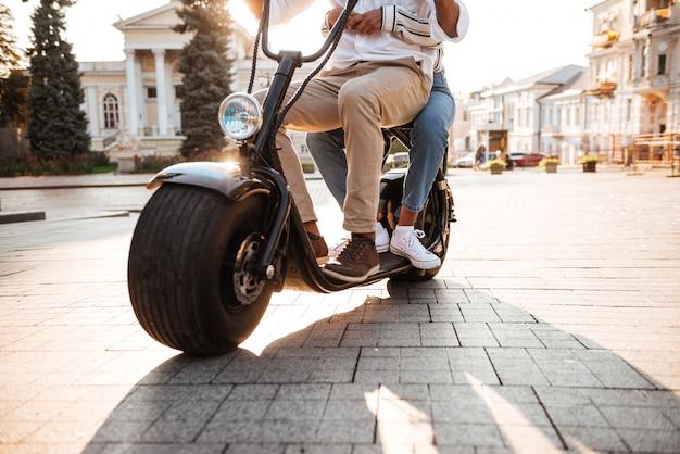 路上で現代のバイクに乗るアフリカのカップルのトリミングされた画像