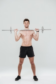 Портрет улыбающегося уверенно спортивный мужчина держит штангу