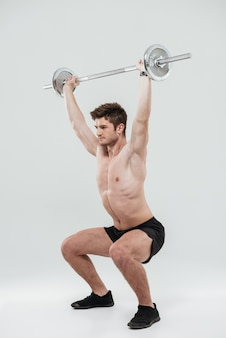 Молодой здоровый человек спортсмен делает упражнения со штангой