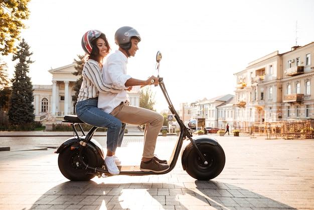 路上で現代のバイクに乗る若いアフリカカップルの完全な長さの側面図