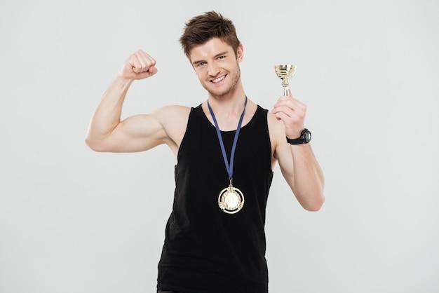 Красивый молодой спортсмен с медалью и наградой