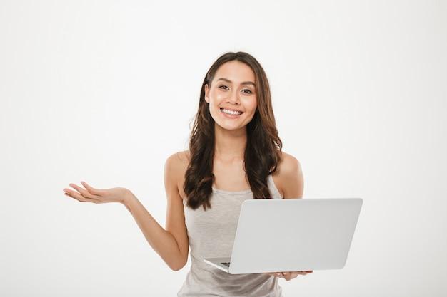 銀のラップトップを保持し、白い壁の上の笑顔で身振りで示す素晴らしい実業家