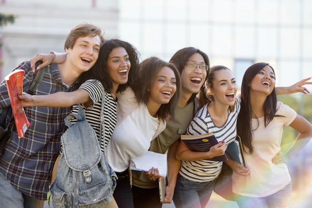 屋外に立っている若い幸せな学生の民族グループ