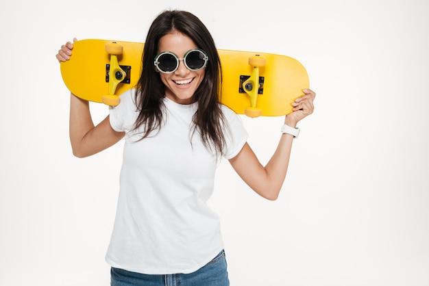 Портрет веселый молодой женщины, держащей скейтборд