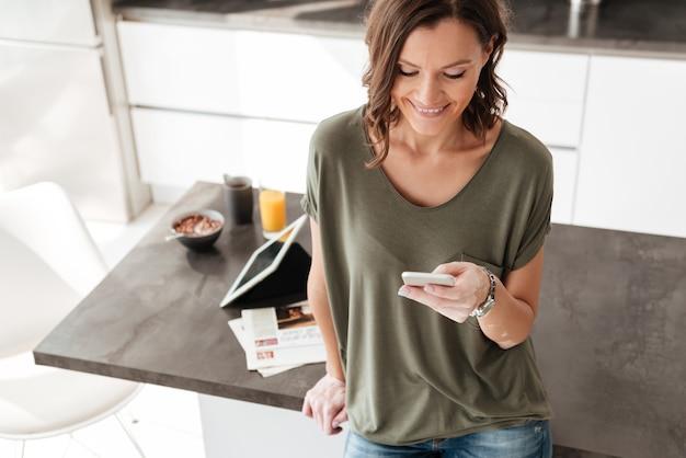 Улыбается женщина текстовых сообщений на мобильный телефон