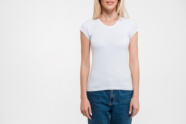 Обрезанное изображение блондинки в футболке и джинсах